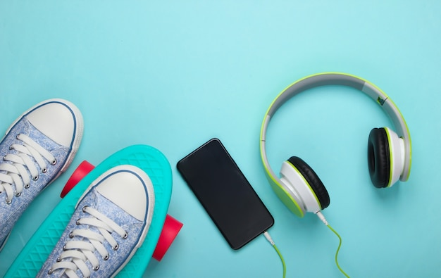 Sneakers on cruiser board and stereo headphones with smartphone on blue pastel surface