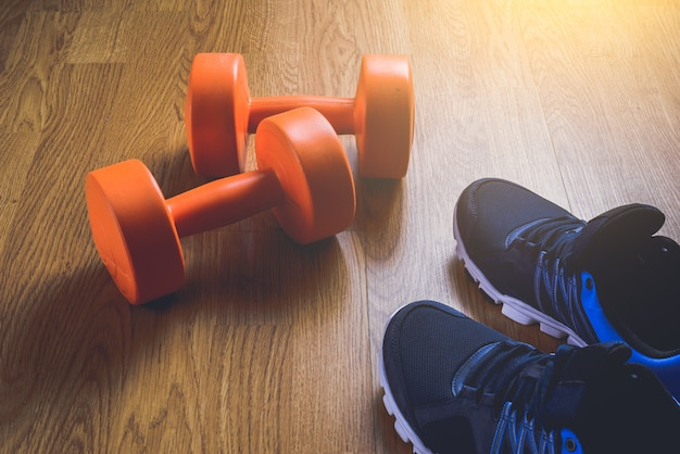 Sneakers and dumbbells fitness on a wooden background.