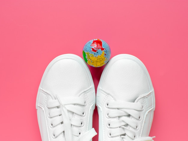Sneakers and the globe on a pink background. life style. concept of travel. top view. flat lay.