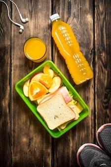 スニーカー、ヘッドホン、オレンジジュース、サンドイッチ、フルーツ。