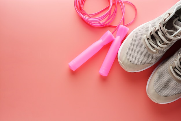 Sneakers and jumping rope over pink background