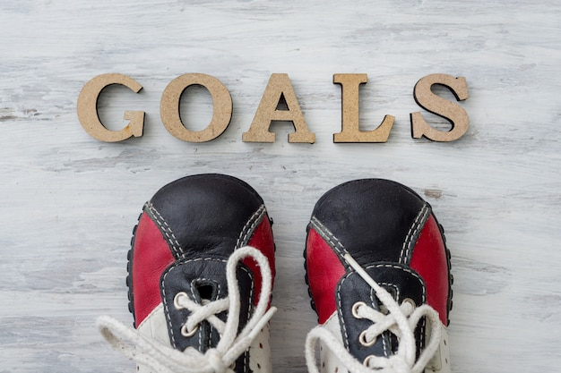 Sneakers on light surface in front of the word goals