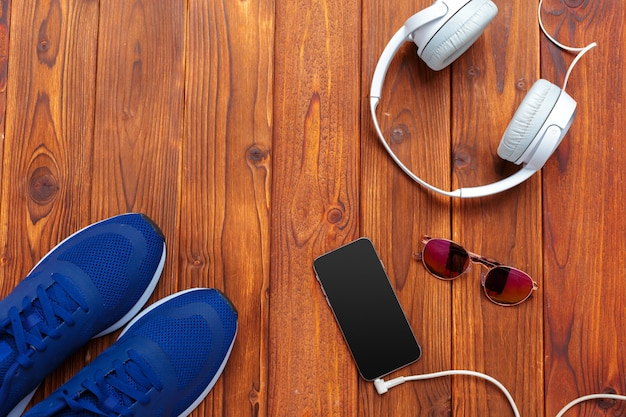 Sneakers and mobile phone with headphones on wooden table