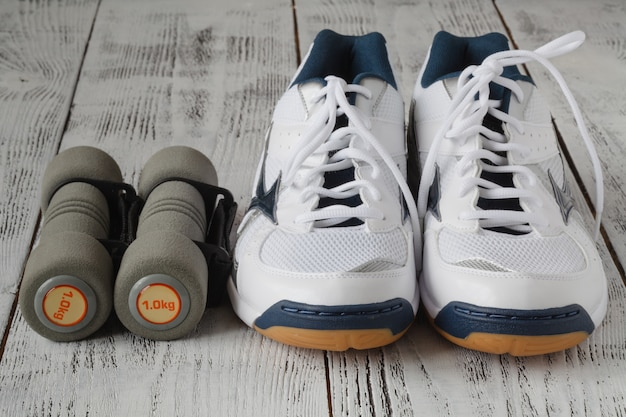 Sneakers and pair of dumbbells on wooden wall. weights for a fitness training.