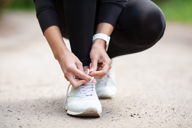 Sneakers problem, female runner tying her shoes preparing for a jog