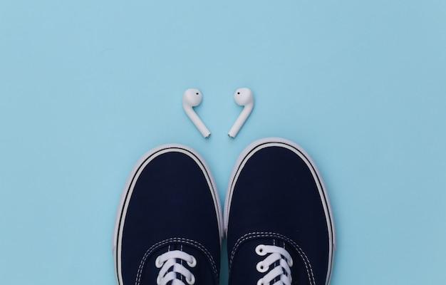 운동화 신발과 파란색 배경에 무선 이어폰.