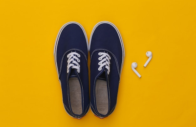 노란색 배경에 운동화 신발과 무선 이어폰.