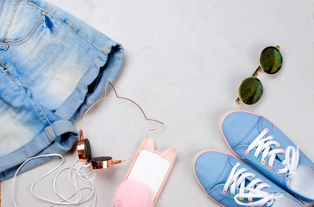 Sneakers, shorts, sunglasses, phone and earphones