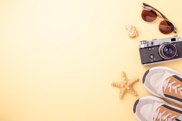Кроссовки, солнцезащитные очки и ретро-камера на желтом фоне. концепция путешествия