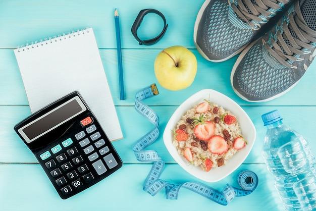 Кроссовки, рулетка, блокнот, калькулятор, бутылка воды, яблоко и овсянка с клубникой и изюмом на синем, плоская планировка