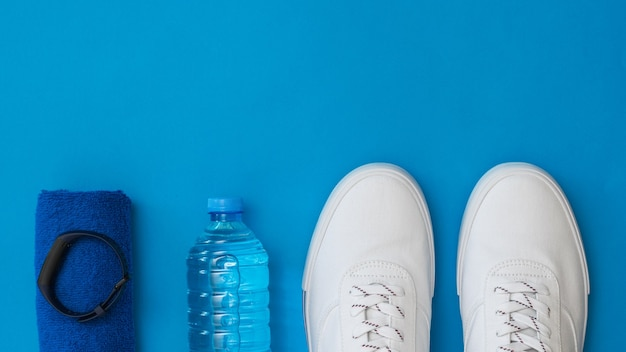 Sneakers, towel, smart bracelet and water on blue surface