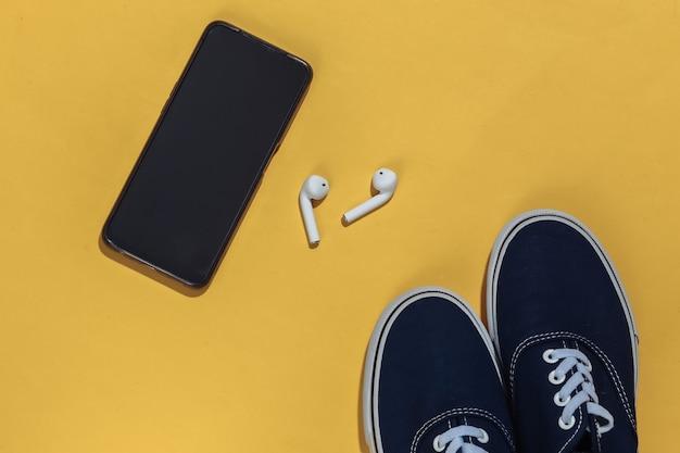 밝은 노란색 배경에 운동화, 무선 헤드폰, 스마트폰.