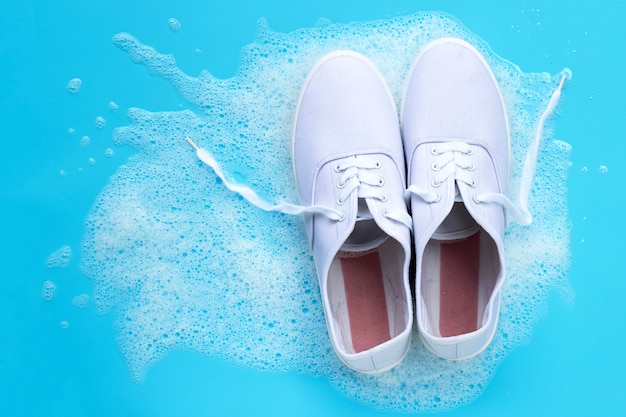 Sneakers with foam of powder detergent water dissolution on blue background. washing dirty shoes.