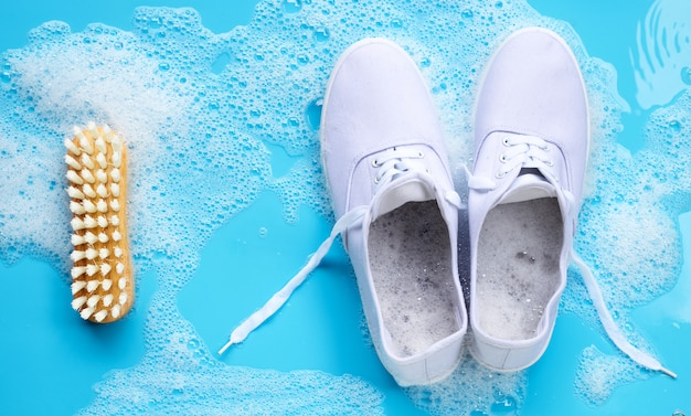 Sneakers with foam of powder detergent water dissolution and wooden brush on blue background. washing dirty shoes.