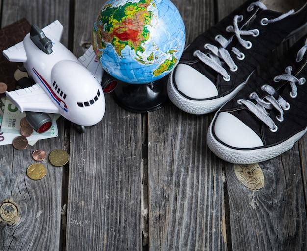 スニーカー、世界の地球儀、お金のある飛行機