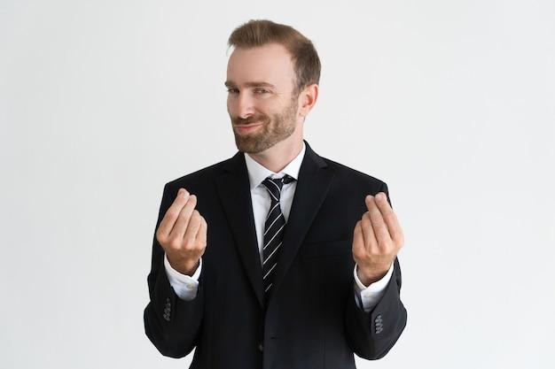 Sneaky деловой человек показывает денежный жест, просят деньги и смотрит на камеру.