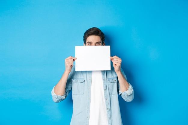 あなたのロゴのために白紙の後ろに顔を隠し、アナウンスをしたり、プロモーションのオファーを示したり、青い背景の上に立っている卑劣なハンサムな男。