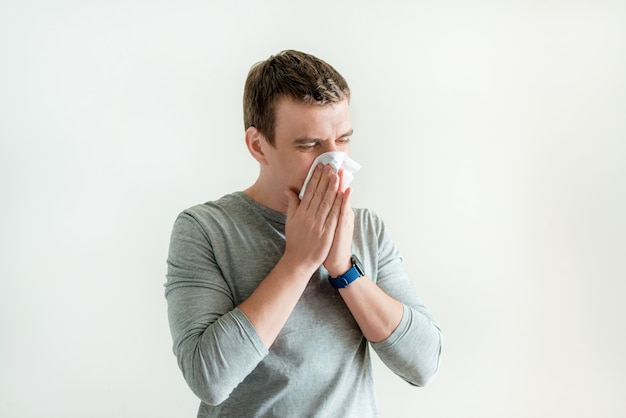 Sneezing man in handkerchief blowing wiping running nose isolated on white background, coronavirus and flusymptoms, respiratory contagious symptoms