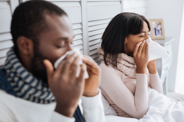 Sneezing people. tired ill couple looking unhappy while staying in their bedroom and sneezing