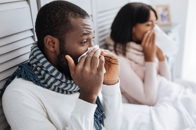 Sneezing together. nice young couple sitting at home and sneezing at the same time while being ill