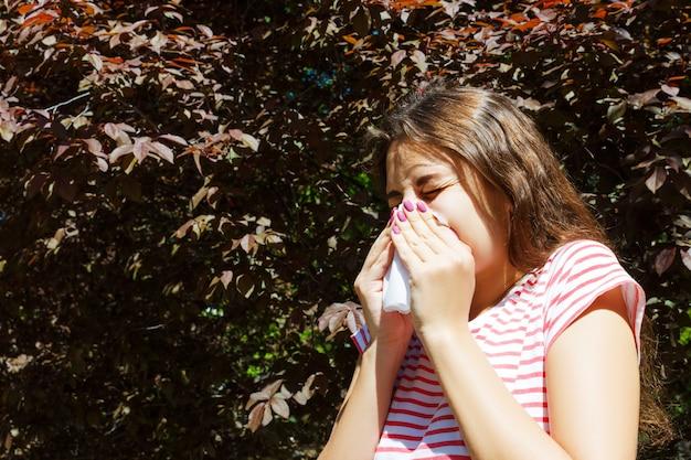Чихая маленькая девочка с салфеткой среди зацветая деревьев в парке. концепция аллергии
