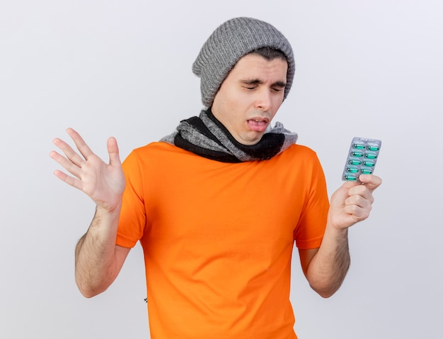 Sneezing young ill man wearing winter hat with scarf holding pills and spread hand isolated on white