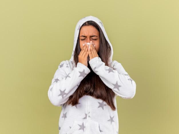 Чихлая молодая больная девушка надевает капюшон, вытирая нос салфеткой, изолированную на оливково-зеленом