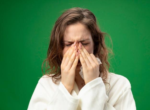 Starnuto giovane ragazza malata che indossa una veste bianca tenendo le mani sul naso isolato su verde