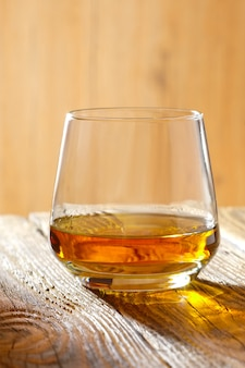 Sniffer glass with whiskey on wooden table in sunlight