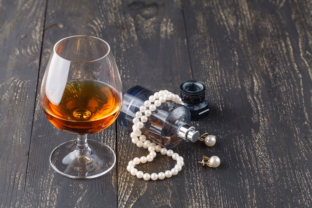 Snifter of brandy in elegant typical cognac glass on black background with female jewelry