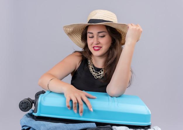 Sniling ragazza giovane viaggiatore che indossa maglietta nera in cappello tenta di valigia chiusa su sfondo bianco