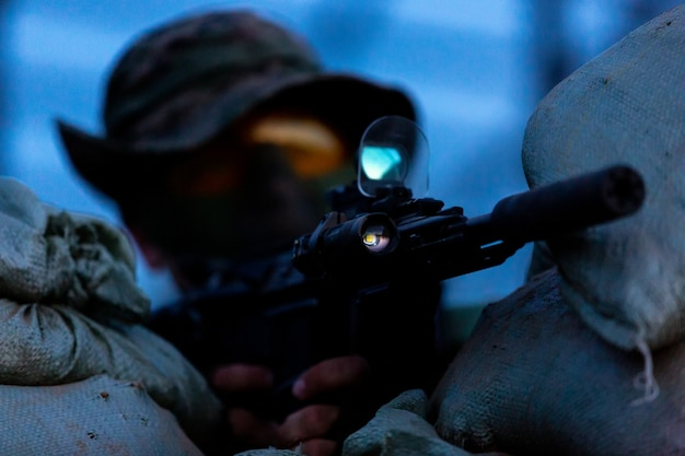 Снайпер вооружен крупнокалиберной снайперской винтовкой, стреляет по вражеским целям на расстоянии от укрытия, сидит в засаде. передний план