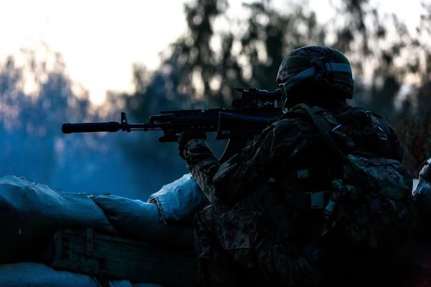 Снайпер вооружен крупнокалиберной снайперской винтовкой, стреляет по вражеским целям на расстоянии от укрытия, сидит в засаде. вид сбоку