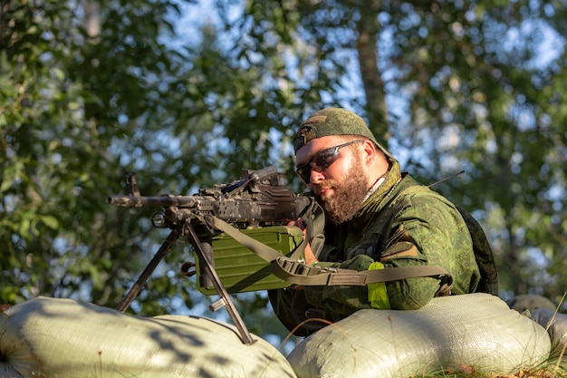大口径のスナイパー、狙撃ライフル、避難所からの範囲で敵のターゲットを撃ち、待ち伏せして座っている