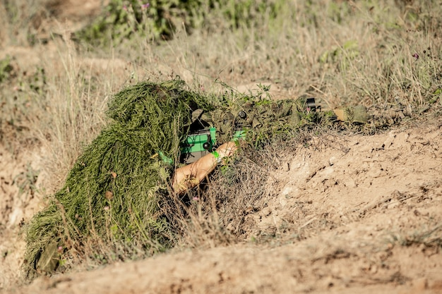 Sniper armed with large caliber, sniper rifle, shooting enemy targets on range from shelter, sitting in ambush.