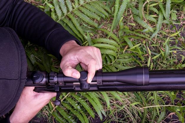 Снайпер регулирует прицел