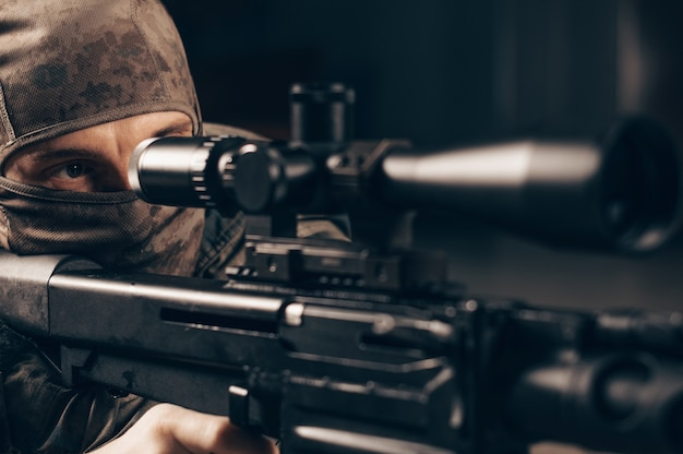 The sniper lies and aims through the telescopic sight.