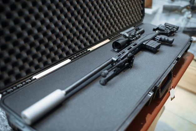 Sniper rifle with optical sight in case closeup, gun shop
