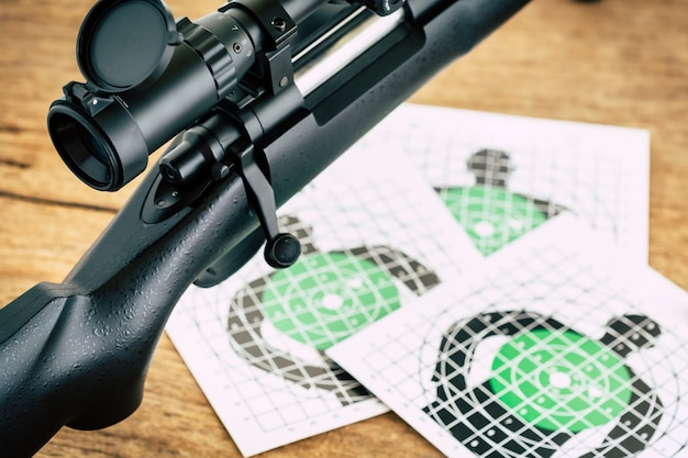Sniper rifle with shooting target on wooden table