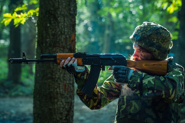 Sniper soldier in army ammunition camouflage and helmet holding rifle and aiming tagret in forest