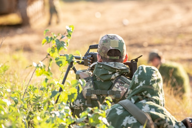 Снайперская бригада, вооруженная крупнокалиберной снайперской винтовкой, стреляет по вражеским целям на расстоянии от укрытия, сидит в засаде