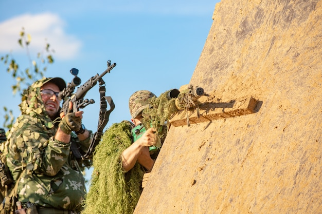 Sniper team armed with large caliber, sniper rifle, shooting enemy targets on range from shelter, sitting in ambush