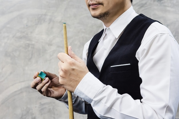 Snooker player standing waiting hold his cue stick and chalk