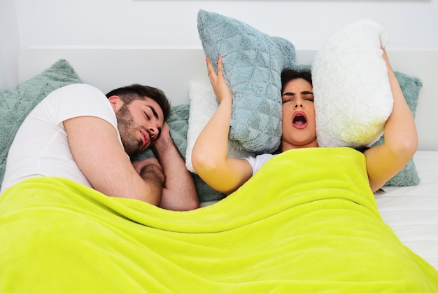 Snoring problems, unable to sleep at night concept. young couple in bed, man snoring, girl covering her ears with pillows.