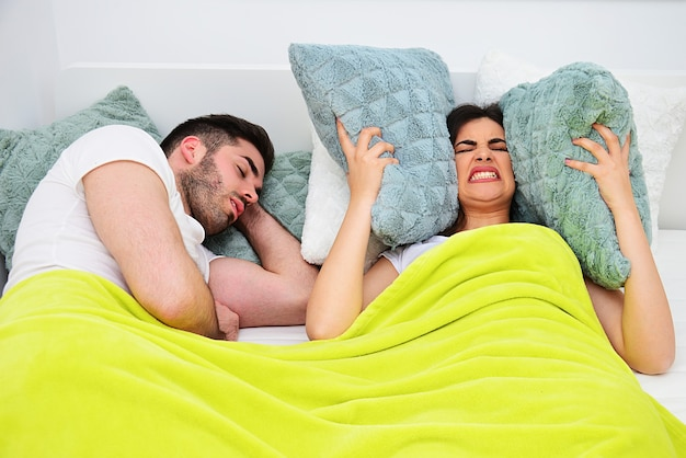 いびきの問題、夜の概念で眠ることができません。ベッドで若いカップル、いびきをかく男、枕で耳を覆っている女の子。