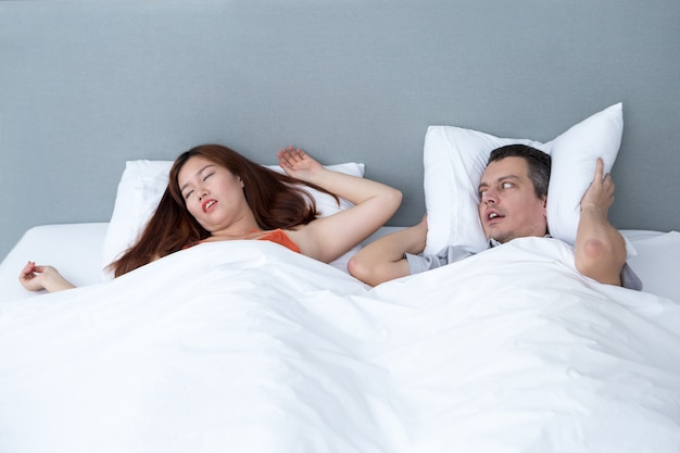 Snoring woman and husband covering ears