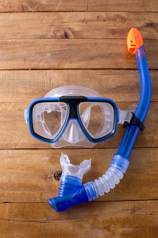 Snorkel and fin on wooden background