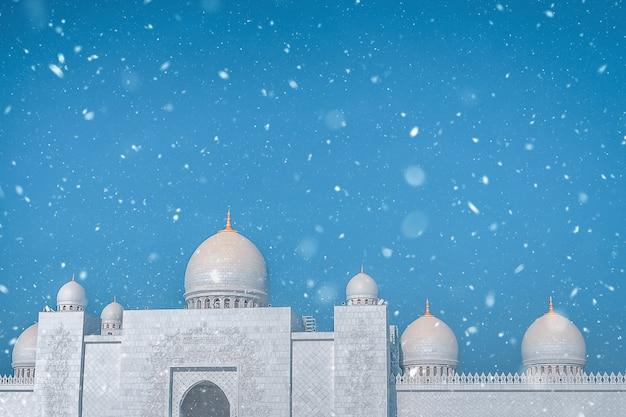 Снег и красивая белая мечеть на фоне голубого неба