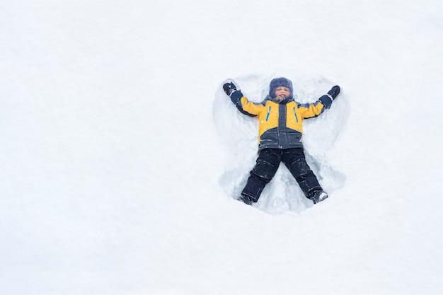 Снежный ангел, сделанный ребенком в желтой куртке в снегу. маленький мальчик зимой лежит на снегу