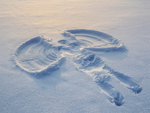 Snow angel made in the white snow in the evening. top flat overhead view.